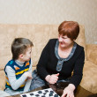 Stock Photo: A grandmother plays with a grandchild in checkers