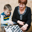 A grandmother plays with a grandchild in checkers — Stock Photo