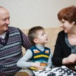 A grandmother, grand-dad, play with a grandchild in checkers — Stock Photo #25831209