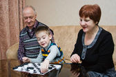 A grandmother, grand-dad, play with a grandchild in checkers — Stock Photo