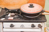Cast-iron frying pan on an old gas-stove on a kitchen — Stock Photo