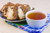 Taza con té caliente y tortas dulces en una servilleta decorativa — Foto de Stock