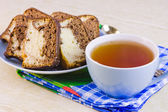Cup with hot tea and sweet cakes on a decorative napkin — Foto de Stock