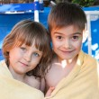 A merry girl and boy are wrapped in a towel — Stock Photo
