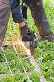 Hombre trabaja fuera, corta un metal — Foto de Stock