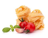 Italian pasta fettuccine nest and cherry tomato — Stock Photo