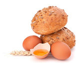 Bun with seeds and broken egg — Stock Photo