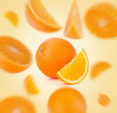 Flying sliced orange fruit segments — Stock Photo
