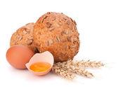 Bun with seeds and broken egg — Stock Photo