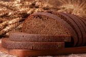 Loaf of bread and rye ears still life — Stock Photo