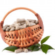 Herbal drug capsules in wicker basket. Alternative medicine conc — Stock Photo