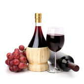 Full red wine glass goblet, bottle and grapes — Stock Photo