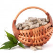 Herbal drug capsules in wicker basket. Alternative medicine conc — Stok fotoğraf
