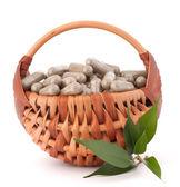 Herbal drug capsules in wicker basket. Alternative medicine conc — Stock Photo
