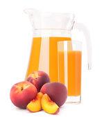 Peach fruit juice in glass jug — Stock Photo