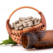 Stock Photo: Herbal drug capsules in wicker basket. Alternative medicine conc