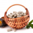 Herbal drug capsules in wicker basket — Stock Photo