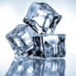 Ice cubes on blue background — Stock Photo