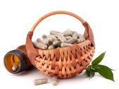 Herbal drug capsules in wicker basket — Stock Photo