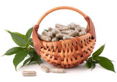 Herbal drug capsules in wicker basket. — Stock Photo