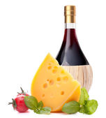 Red wine bottle, cheese and tomato still life  — Stock Photo
