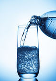 Pouring water into glass  from bottle — Stock Photo