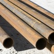 Stack of rusty old pipes - Stock Photo