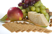 Apple, grape, nuts and cheese lying on a plate. — Stock Photo