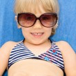 Little girl with sunglasses in a deck chair — Stock Photo