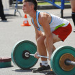 Young athlete raises the barbell — Stock Photo