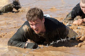 Man crawling on a mud puddle — Stockfoto