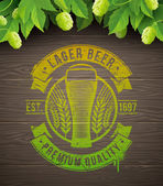 Beer emblem painted on wooden surface and ripe hops and leaves - vector illustration — Wektor stockowy