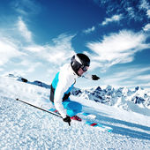 Skier in mountains, prepared piste and sunny day — Stok fotoğraf