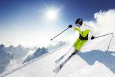 Skiër in bergen, bereid piste en zonnige dag — Stockfoto