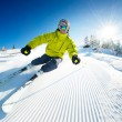 Skier in mountains, prepared piste and sunny day - Foto Stock