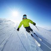Esquiador nas montanhas, piste preparado e dia ensolarado — Foto Stock