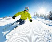 Skidåkare i bergen, beredda pisten och solig dag — Stockfoto