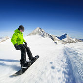 Snowboarder on piste in high mountains — Stock Photo