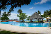 Pool with artificial beach and tropical ocean — Stock Photo