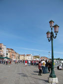 Lantern and tourists at embankment in Venice (Italy) — Stock Photo