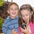 Stock Photo: Little girl and boy in a park with a mobile phone