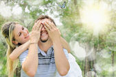 Smiling girl covering the eyes of her boyfriend — Stock Photo