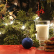 Cup of milk with cookies under Christmas tree - Stock Photo