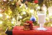 Kopje melk met cookies op de tabel onder de kerstboom — Stockfoto