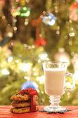 Glas melk met cookies onder kerstboom — Stockfoto