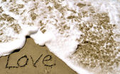 Love written in the sand with wave 4-1 — Stock Photo