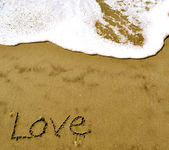 Love written in the sand with wave-1-1 — Stock Photo