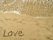 Love written in the sand with wave 13-1 — Stock Photo