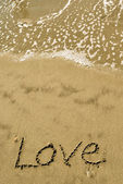 Love written in the sand with wave 14-1 — Stock Photo