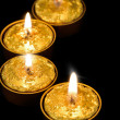 Golden candles on a black background. - Foto Stock